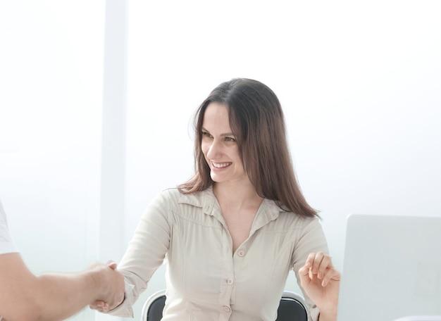 Z bliska. biznesmenka, ściskając ręce ze swoim partnerem biznesowym