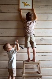Z bliska chłopcy powiesić zdjęcie w drewnianym domu