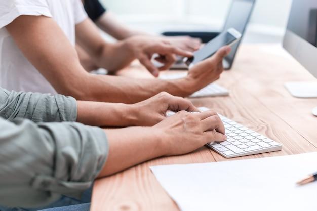 Z bliska grupa pracowników korzysta z urządzeń w biurze ludzie i technologia