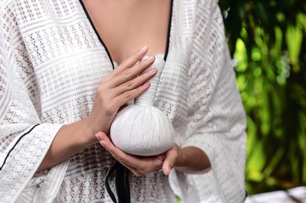 Z bliska: kobiece dłonie trzymające ciepłą ziołową piłkę do masażu tajskiego
