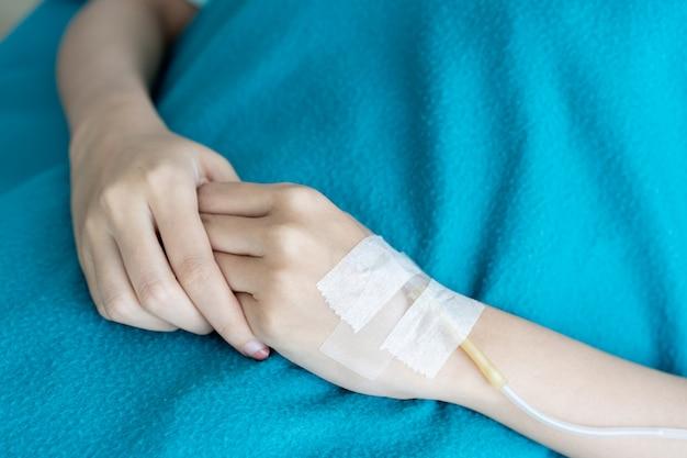 Z bliska na rękach kobiety, pacjentka zostaje w szpitalu i otrzymuje dożylnie płynny roztwór soli fizjologicznej. zdrowa opieka i wellness w koncepcji nowoczesnego stylu życia.