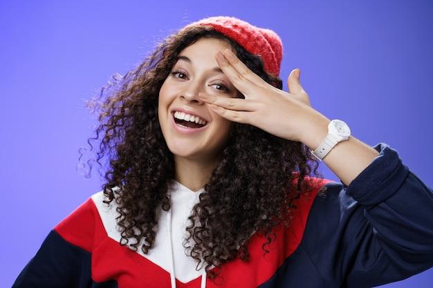 Z bliska strzał charyzmatyczny szczęśliwy beztroski kobiety w zimie czerwona śliczna czapka i bluza trzymając palce w pobliżu oka i zerkając z szerokim uśmiechem na aparat zabawy, grając na niebieskim tle.