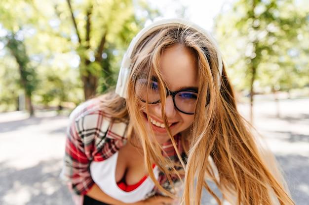 Z bliska strzał entuzjastycznej dziewczyny długowłosej w słuchawkach. młoda dama w okularach wygłupiać się w lato park.