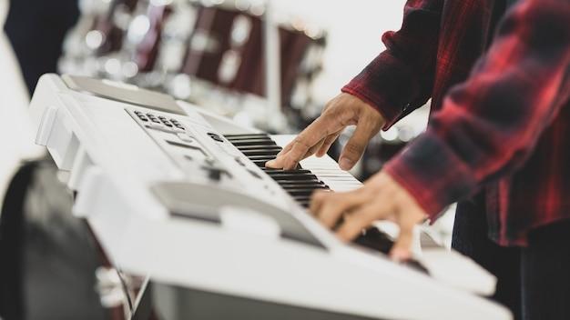 Z bliska strzał męski muzyk ręce gra na klawiaturze elektrycznej. selektywna koncentracja na rękach z bębnem w tle. profesjonalny pianista ćwiczący i ćwiczący przygotowuje się do konkursu