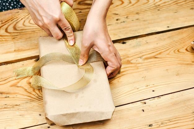Z bliska strzał ręce kobiety pakowania prezentów świątecznych w domu. twórz prezenty świąteczne. diy prezenty świąteczne dla rodziny