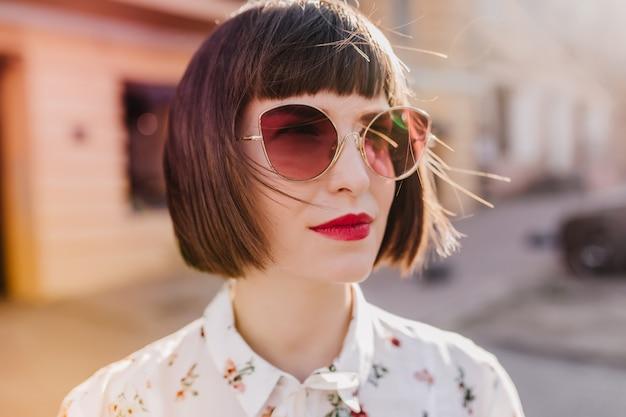 Z bliska strzał wspaniałej europejskiej dziewczyny w białej bluzce. zewnątrz zdjęcie uroczej kobiety w ciemnych okularach przeciwsłonecznych.