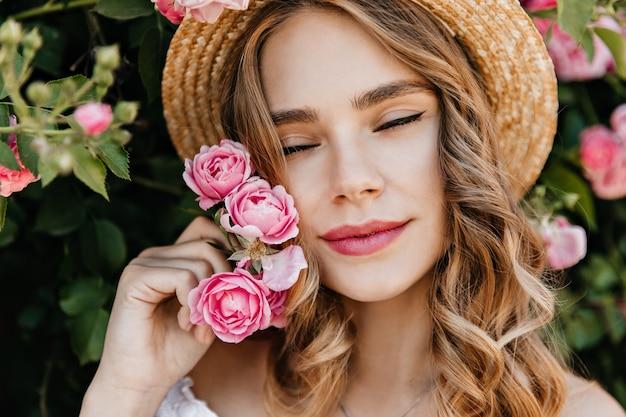 Z bliska strzał zainspirowanej kobiety rasy kaukaskiej gospodarstwa różowy kwiat. zewnątrz portret wyrafinowanej blondynki pani chłodzi w ogrodzie.