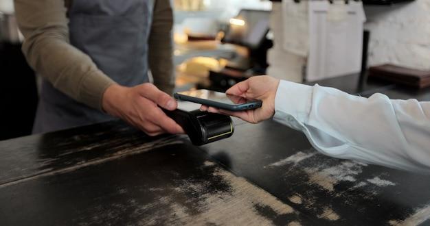 Z bliska w kawiarni mężczyzna robi kawę na wynos dla klienta płaci zbliżeniowym telefonem komórkowym