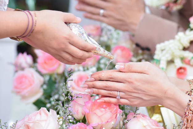 Z bliska wylewanie błogosławieństwa wody w ręce panny młodej, tajskie wesele