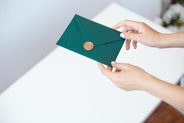 Z bliska zdjęcie kobiecych rąk trzymających zieloną kopertę z woskową pieczęcią, bon upominkowy, pocztówka, karta zaproszenia na ślub.