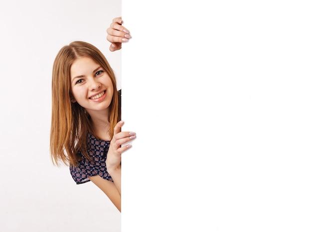 Z boku billboardu pojawia się młoda kobieta.