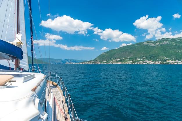 Z boku jachtu widoczny jest malowniczy krajobraz.