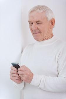 Z czasem. pewny siebie starszy mężczyzna trzymający telefon komórkowy, opierając się o ścianę