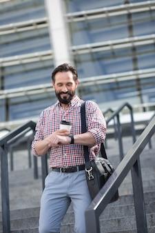 Z czasem. przyjemny uśmiechnięty mężczyzna sprawdzający czas podczas picia kawy