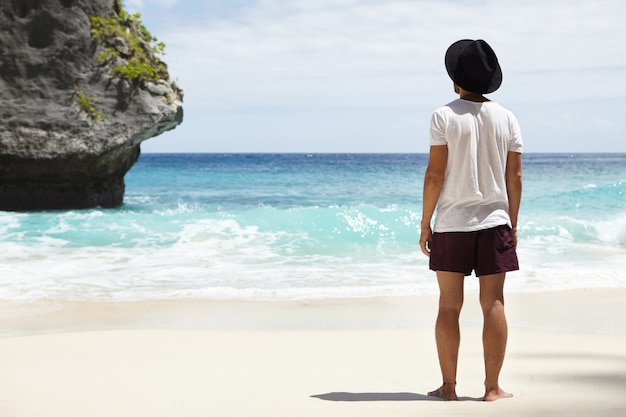 Z dala od szlaków turystycznych. boso młody kaukaski poszukiwacz przygód, stojący na piaszczystym brzegu przed kamienną wyspą na turkusowym oceanie, który w końcu znalazł podczas swojej długiej podróży wzdłuż wybrzeża