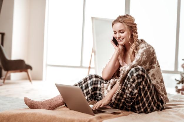 Z długimi włosami. wesoła kobieta z szerokim uśmiechem, siedząca na łóżku w ciepłych puszystych skarpetkach i prowadząca satysfakcjonujący dialog