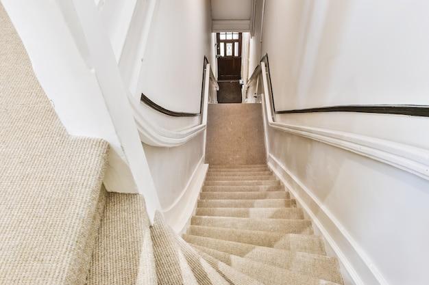 Z dołu widok perspektywiczny schodów na górną kondygnację z poręczami i wykładziną na schodach