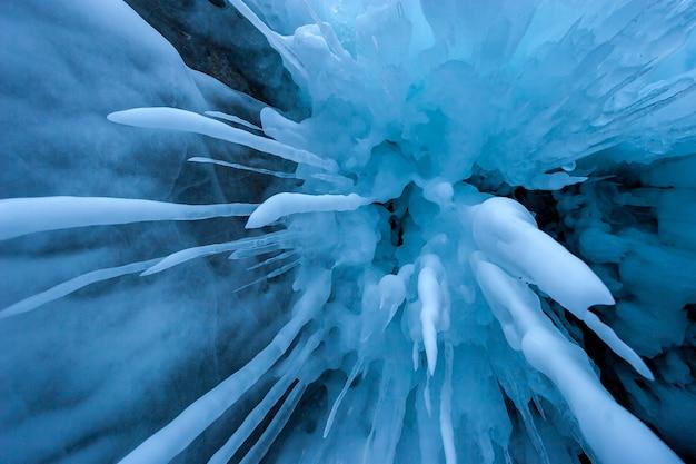 Z dołu wystrzeliły długie stopione sople. ostre sople w kolorze niebieskim. wokół dużo lodu. zimowe zamrożone tło.