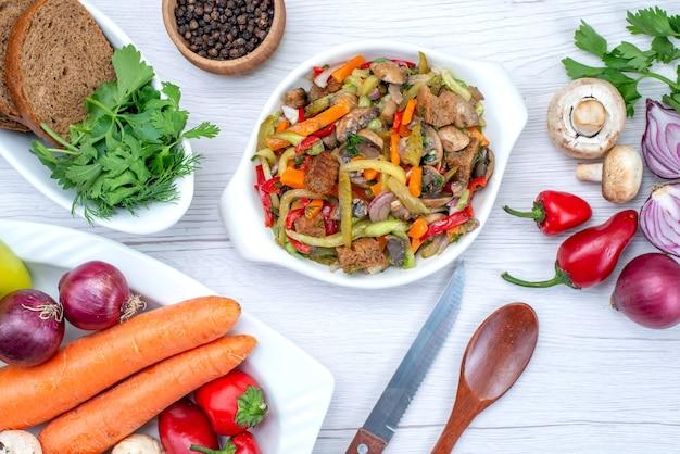Z góry bliżej widoku sałatki ze świeżych warzyw pokrojonej z mięsem wraz z bochenkami chleba i całymi warzywami i zieleniną na lekkim biurku