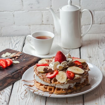 Z góry ciasto waflowe z truskawkami i filiżanką i czajnikiem w okrągłym białym talerzu