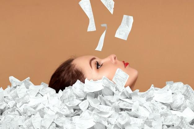 Z góry czeków i rachunków wystaje twarz pięknej dziewczyny. osoba tonie w długach, kredycie, hipotece, pożyczce, hipotece.