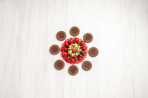 Z góry daleki widok ciasto jagodowe na czerwonej owalnej serwetce z ciasteczkami na białym drewnianym stole