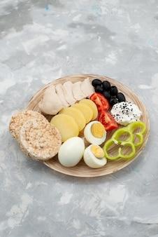 Z góry daleki widok jajka na twardo z piersiami oliwek i pomidorami na szarym, warzywnym posiłku śniadaniowym