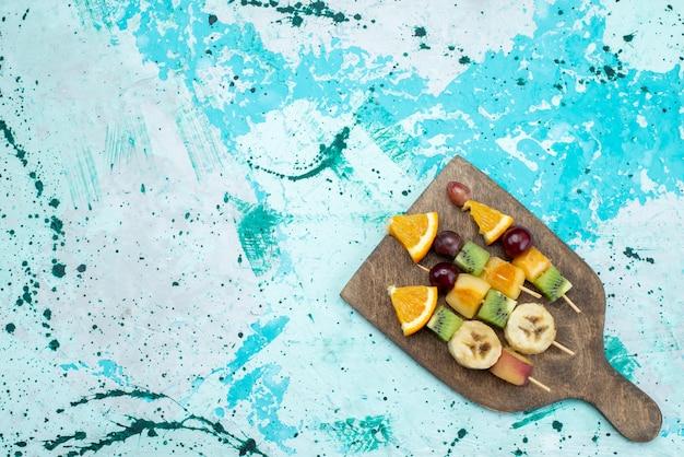 Z góry daleki widok kompozycja owocowa pokrojona na patyczkach na jasnym biurku owoce egzotyczne ciasteczka cukier