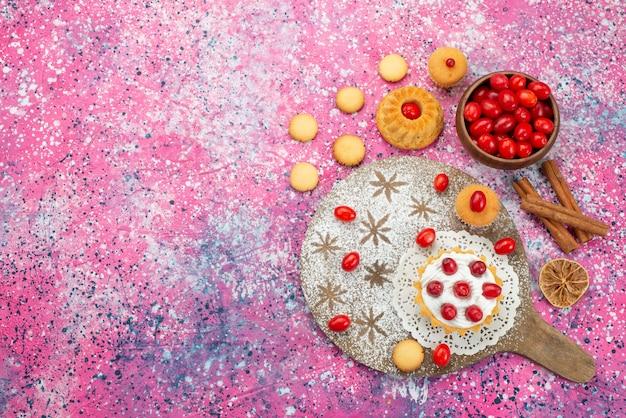 Z góry daleki widok kremowy tort ze świeżą czerwoną żurawiną wraz z cynamonowymi ciasteczkami na fioletowej podłodze herbatniki słodkie owoce jagodowe