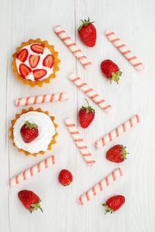 Z góry daleki widok małych kremowych ciastek ze świeżymi truskawkami i cukierkami na lekkim, słodkim ciastku z jagodami