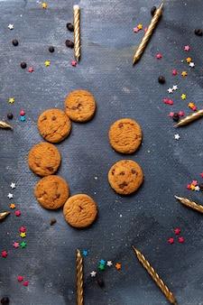 Z góry daleki widok pyszne czekoladowe ciasteczka ze świecami na ciemnoszarym biurku ciastko herbaciane słodka herbata cukier