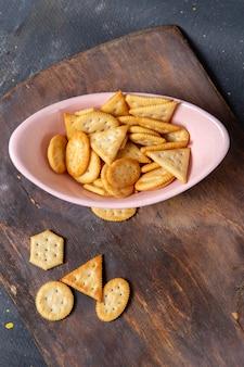 Z góry daleki widok różowy talerz z krakersami i chipsami na drewnianym biurku i zdjęcie z przekąską z szarego tła krakersa
