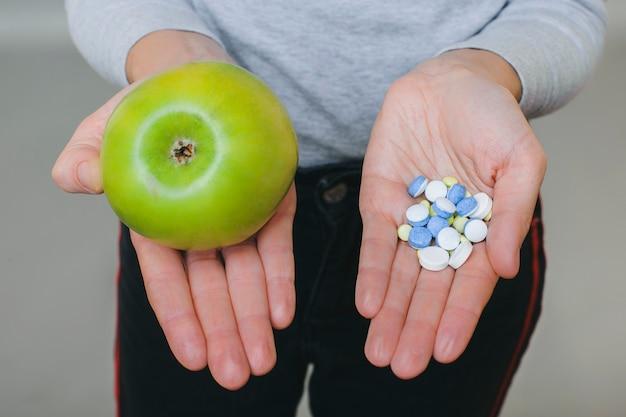 Z góry kobieta uprawna pokazująca świeże zielone jabłko i stos lekarstwa na dłoniach na szaro