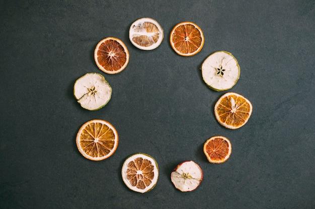 Z góry kompozycja suchych pomarańczy i jabłek w kształcie okrągłych na czarnym