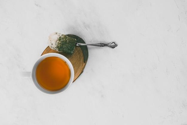 Z góry kubek gorącej herbaty na kawałku drewna obok łyżki i mokrej torebki