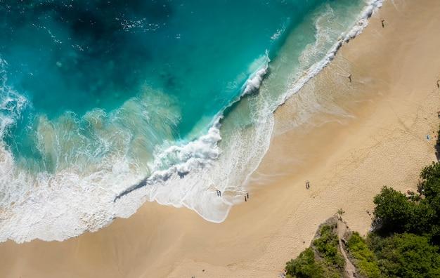 Z góry na dół drone strzał z dużych fal plaży kelingking w nusa penida, bali - indonezja