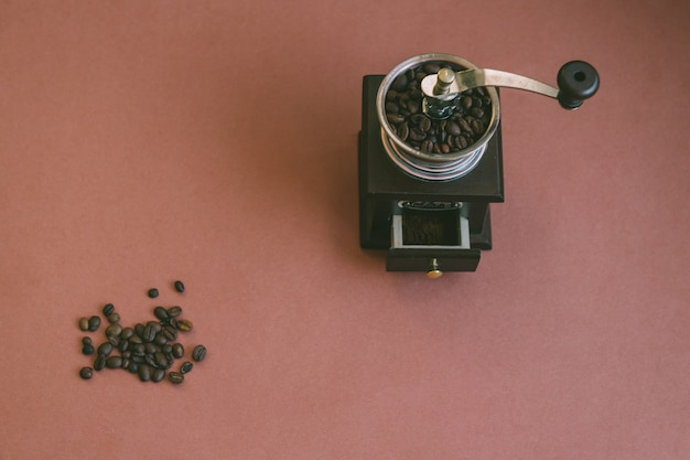 Z góry na dół nastrojowe, nastrojowe zdjęcie garstki ziaren kawy leżących razem z ręcznym drewnianym młynkiem do kawy w stylu retro