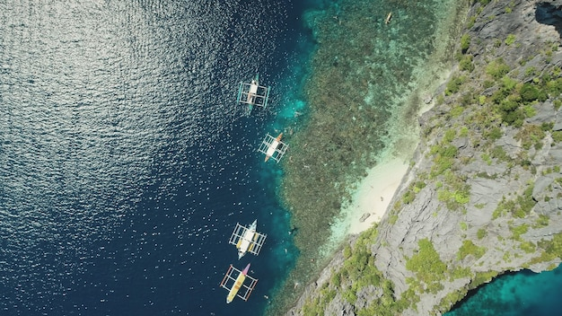 Z góry na dół tradycyjnych łodzi na skalistym wybrzeżu oceanu z lotu ptaka. majestatyczny krajobraz ze statkami na słońcu