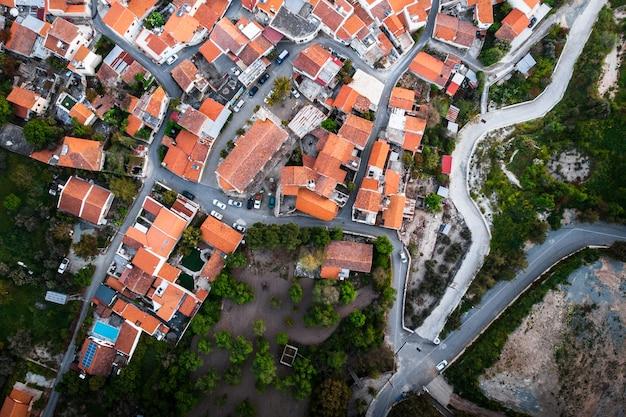 Z góry na dół widok z lotu ptaka na czerwone dachy domów w małej wiosce.