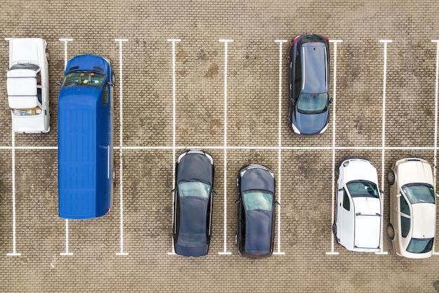 Z góry na dół widok z lotu ptaka wielu samochodów na parkingu przy supermarkecie lub na rynku sprzedaży samochodów.
