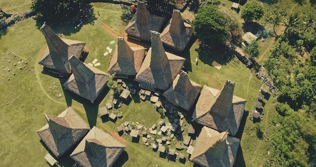 Z góry na dół wycieczki turystyczne po dachach tradycyjnych domów prymitywnej wioski na wyspie sumba w indonezji. niesamowite letnie wakacje admirał zieloną dziką przyrodę i wyjątkowy indonezyjski punkt orientacyjny podczas ujęcia z drona