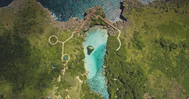 Z góry na dół zaprojektowanej ścieżki nad lazurowym jeziorem na zielonym brzegu klifu z lotu ptaka. zieleń tropikalna łąka z drzewami, trawami na wybrzeżu oceanu. epicki krajobraz z weekuri landmark, sumba island, indonezja
