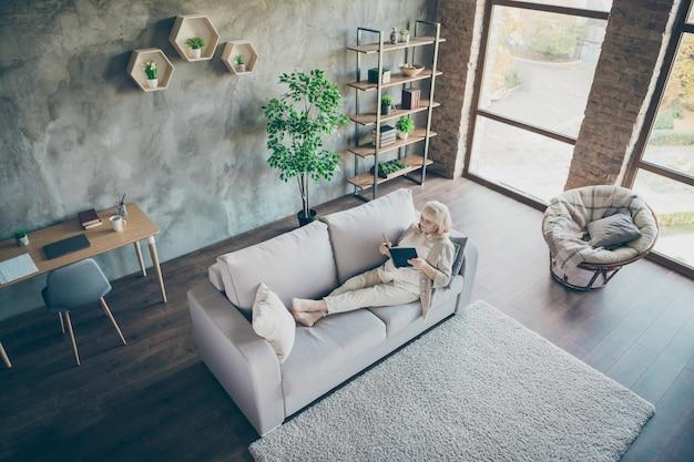 Z góry nad wysokim kątem jej widok jest ładna, śliczna, skupiona siwowłosa blond babcia w średnim wieku czytająca historię miłosną na otwartej przestrzeni industrialny ceglany loft nowoczesny styl wnętrze domu mieszkanie