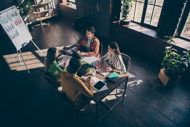Z góry nad wysokim kątem widzenia czterech zajętych, wykwalifikowanych biznesmenów w strategii planowania planu finansowego rozwiązania casual formalnych