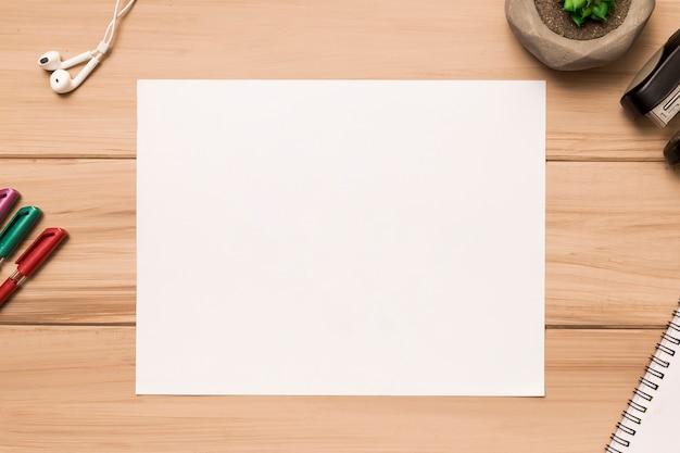 Z góry pusty arkusz papieru otoczony materiałami biurowymi