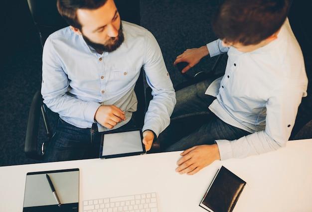 Z góry ujęcie dwóch mężczyzn siedzących przy biurku i korzystających razem z nowoczesnego tabletu z pustym wyświetlaczem. koledzy używający tabletu z pustym ekranem