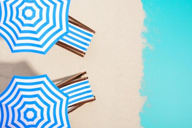 Z góry ujęcie pasiastych krzeseł pod parasolami na plaży.