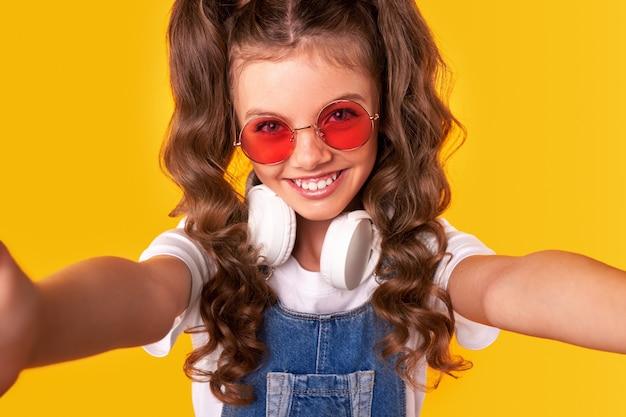 Z góry uśmiechnięta nastolatka z kręconymi włosami iw modnym stroju przy selfie