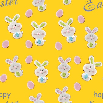 Z góry widok na kolorowe glazurowane imbirowe ciasteczka na żółtym tle z szarymi napisami. zbliżenie na piękne pyszne domowe ciasto w kształcie zające wielkanocne i jajka.
