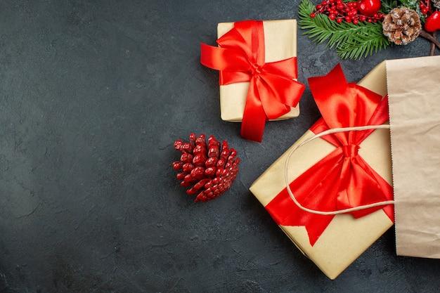 Z góry widok świątecznego nastroju z szyszkami iglastymi i prezentowymi gałęziami jodły po prawej stronie na ciemnym stole